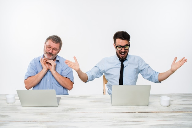 Die zwei kollegen arbeiten zusammen im büro auf weißem hintergrund. beide schauen auf die computerbildschirme. beide überrascht. konzept der positiven emotionen und guten nachrichten