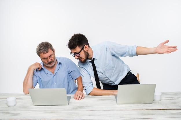 Die zwei kollegen arbeiten zusammen im büro auf weißem hintergrund. sie diskutieren etwas. beide schauen auf einen computerbildschirm
