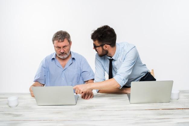 Die zwei kollegen arbeiten zusammen im büro auf weißem hintergrund