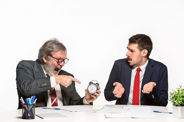 Die zwei kollegen arbeiten zusammen im büro auf weißem hintergrund.