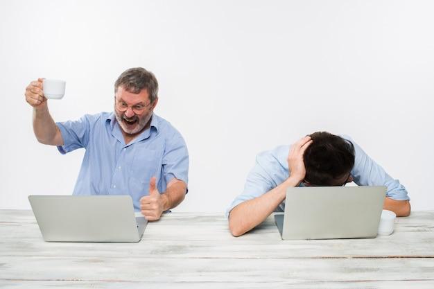 Die zwei kollegen, die im büro auf weißem hintergrund zusammenarbeiten