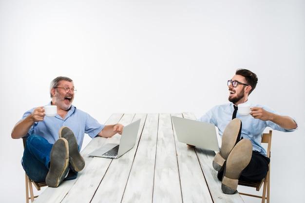 Die zwei lächelnden geschäftsleute mit den beinen über dem tisch, der an laptops auf weißem hintergrund arbeitet. geschäft im amerikanischen stil