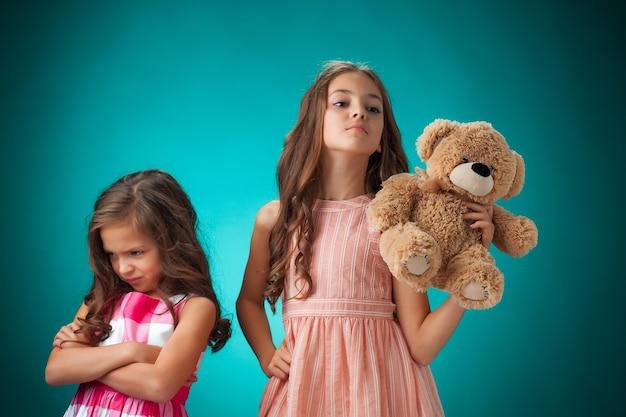 Die zwei niedlichen kleinen mädchen auf blauem hintergrund mit teddybär