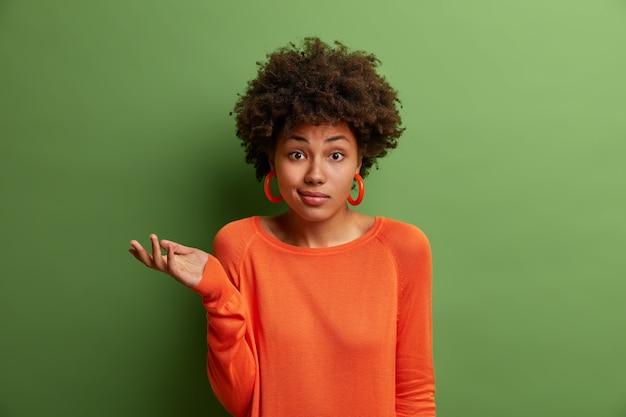 Die zweifelhafte unentschlossene frau hebt zögernd die handfläche, steht vor schwierigen fragen oder zwei entscheidungen, trägt einen orangefarbenen pullover und ohrringe, die auf einer grünen wand isoliert sind. menschen, wahrnehmung und einstellung