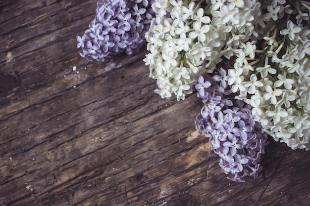Die zweige von lila flieder auf dunklem holzhintergrund. gefallene lila blumen auf dem tisch. platz für text. selektiver fokus. valentinstag und muttertag hintergrund.