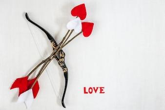 Die Zweigpfeile, der Bogen und die Buchstaben des handgemachten Amors LIEBEN auf einem weißen hölzernen Hintergrund.