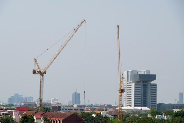 Die zwillingshochkräne arbeiten über dem geschäftsgebäude, um das moderne bürogebäude im universitätsbereich zu errichten, frontansicht für den hintergrund.