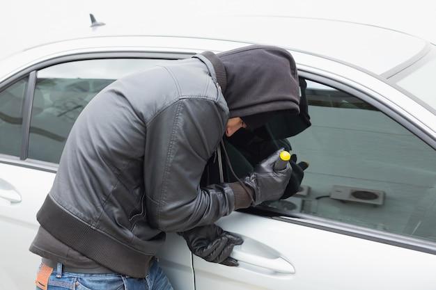 Dieb, der mit schraubenzieher in auto einbricht