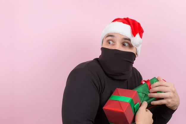 Dieb in rotem hut stiehlt fremde weihnachtsgeschenke