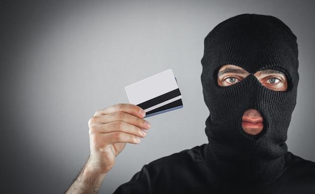 Dieb in schwarzer sturmhaube hält eine kreditkarte.