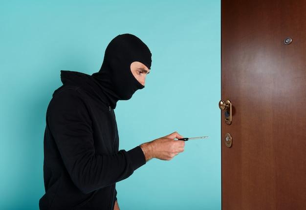 Dieb mit sturmhaube versucht die wohnungstür mit einem schlüssel zu öffnen