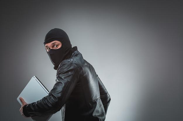 Dieb stiehlt einen laptop. auf grauem hintergrund isoliert