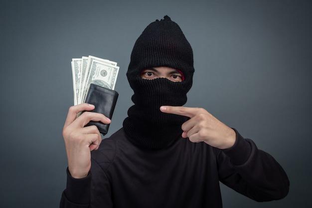 Dieb trägt einen schwarzen hut mit einer gestohlenen handtasche auf grau
