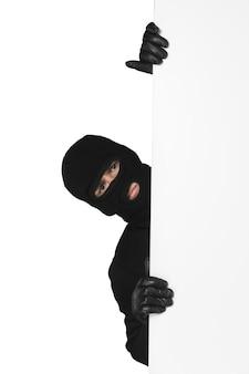 Dieb versteckt sich hinter einem leeren weißen schild mit platz für text auf weißem hintergrund