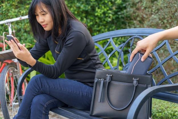 Dieb versucht zu stehlen und gehen sie die brieftasche während frau mit handy und sitzen