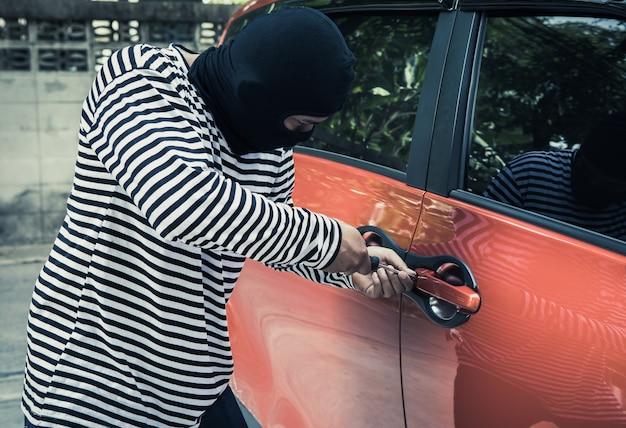 Diebe versuchen, schraubenzieher zu verwenden, öffnen die autotür, stehlen auto, während der eigentümer des autos tut