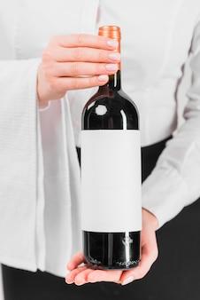 Diener, der eine flasche wein zeigt