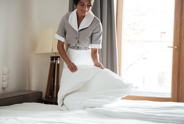 Dienstmädchen, das weißes bettlaken im hotelzimmer aufstellt
