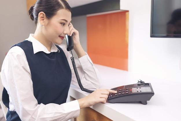 Dienstmädchen in blauer uniform mit telefon im hotelzimmer