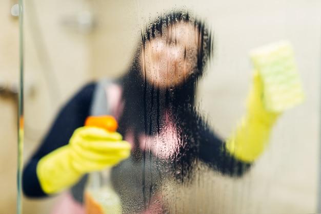 Dienstmädchen in handschuhen reinigt glas mit einem reinigungsspray