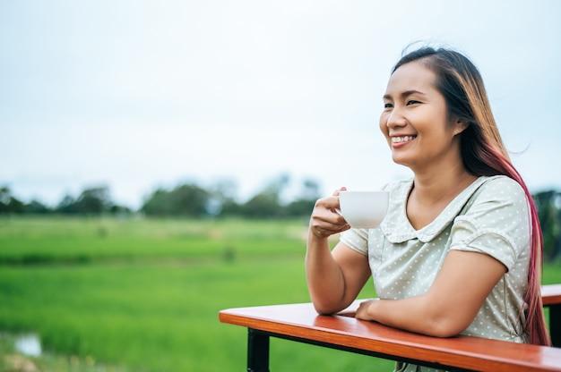 Diese frau stand glücklich auf der wiese und trank kaffee.