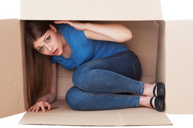 Diese kiste ist zu klein. schockierte junge frau, die beim sitzen in einem karton in die kamera schaut