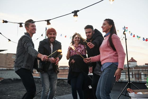 Diese leute freuen sich, zusammen zu feiern. spielen mit wunderkerzen auf dem dach. gruppe junger schöner freunde