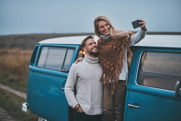 Dieser geht in den rahmen. schönes junges paar, das selfie nimmt und lächelt, während sie ihre straßenreise genießen