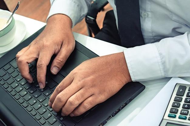 Dieser karrieregeschäftsmann mit computerlaptop mit taschenrechner