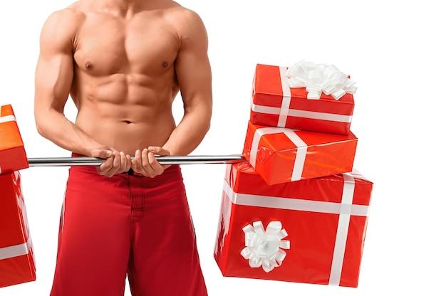 Dieser körper ist selbst ein geschenk. horizontale nahaufnahme eines starken muskulösen mannes, der mit geschenken im studio, isoliert auf weiß, trainiert