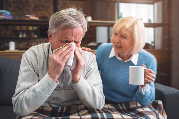 Dieser kranke mann niest in die serviette. seine frau sitzt neben hijm
