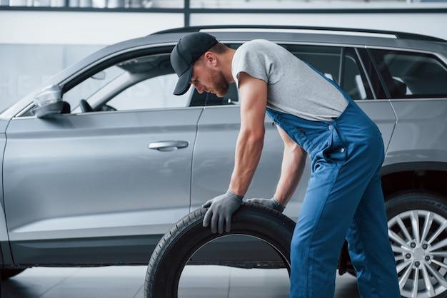 Dieser muss perfekt passen. mechaniker hält einen reifen in der reparaturwerkstatt. austausch von winter- und sommerreifen