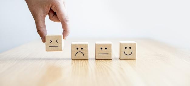 Dieser quadratische holzblock mit emoticons wird verwendet, damit kunden ihre zufriedenheit nach der nutzung des dienstes beurteilen können. panoramafahnenhintergrund mit kopienraum.