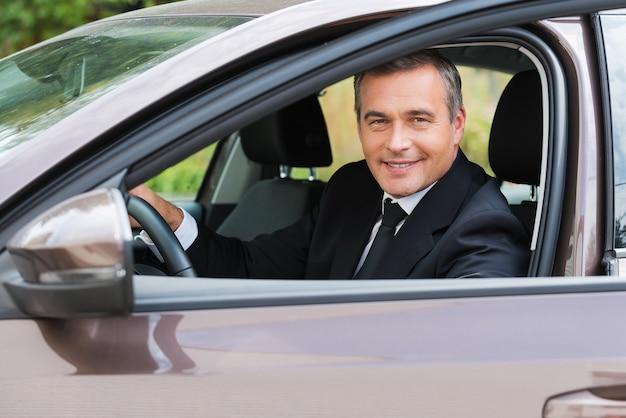 Dieses auto ist einfach perfekt! fröhlicher reifer mann in formeller kleidung, der auto anschaut und lächelt, während er im auto sitzt