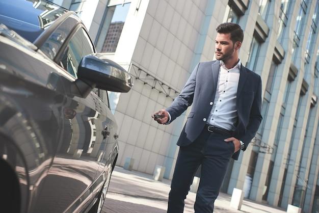 Dieses auto ist perfekt für mich, ein fröhlicher reifer mann in formeller kleidung, der in die kamera schaut und