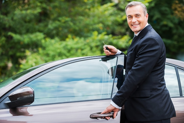 Dieses auto ist perfekt für mich. fröhlicher reifer mann in formeller kleidung, der die kamera anschaut und lächelt, während er in der nähe seines neuen autos steht