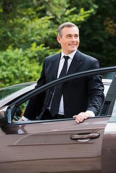 Dieses auto ist perfekt für mich. fröhlicher reifer mann in formeller kleidung, der wegschaut und lächelt, während er aus dem auto aussteigt