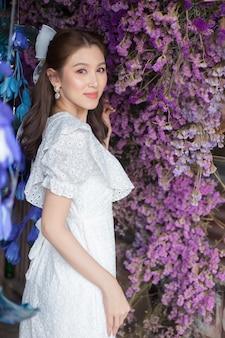 Dieses bild einer schönen asiatischen frau in einem weißen kleid steht gut gelaunt unter