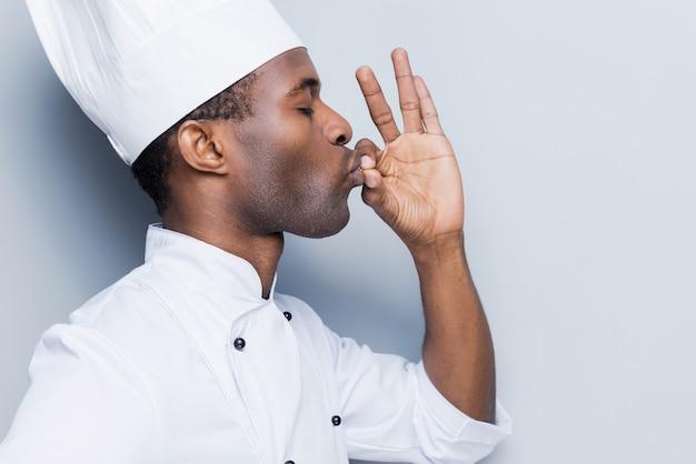 Dieses essen ist einfach perfekt! seitenansicht des selbstbewussten jungen afrikanischen kochs