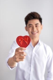Dieses geschenk ist für dich. ein lächelnder eleganter mann in einem weißen hemd mit geschenken in den händen zeigt sie der kamera.