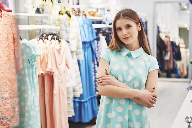 Dieses kleid ist perfekt rückansicht der schönen jungen frau, die kleid anprobiert und ihr spiegelbild im spiegel betrachtet, während sie in der umkleidekabine im laden steht
