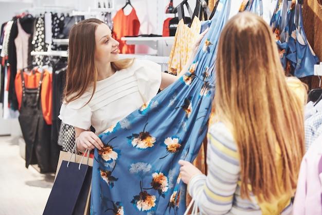 Dieses kleid ist perfekt, schauen sie sich nur den preis an. zwei schöne mädchen wählen kleidung im einkaufszentrum. der lieblingsberuf für alle frauen, einkaufskonzept