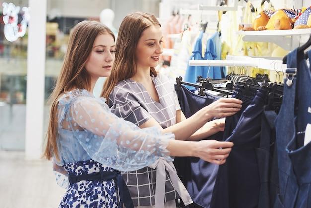 Dieses kleid ist perfekt, schauen sie sich nur den preis an. zwei schöne mädchen wählen kleidung im einkaufszentrum. der lieblingsberuf für alle frauen, einkaufskonzept.