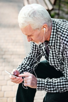 Dieses lied. draufsicht des ernsten älteren mannes, der kopfhörer aufsetzt und musik hört