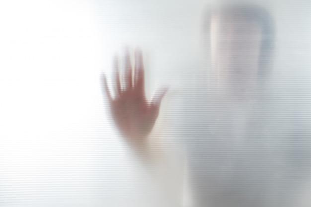 Diffuse silhouette der weiblichen hände, ansicht mit schatten durch plastik