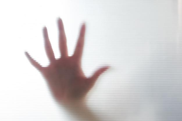 Diffuse silhouette der weiblichen hände durch plastik