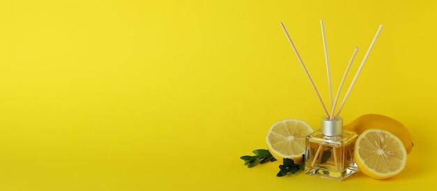 Diffusor, zitronen und blätter auf gelbem hintergrund