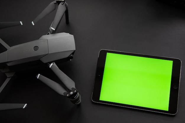 Digital tablet-touchscreen-gerät mit leerem grünem bildschirm, der an drone copter angeschlossen ist