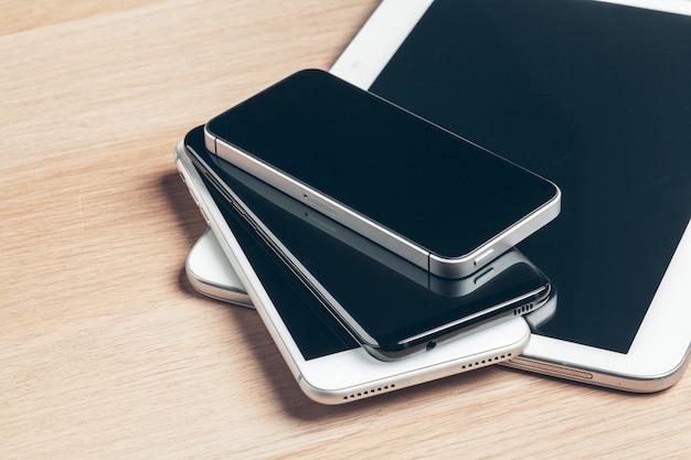 Digital tablet und handy. elektronische geräte auf holztisch, abschluss oben.