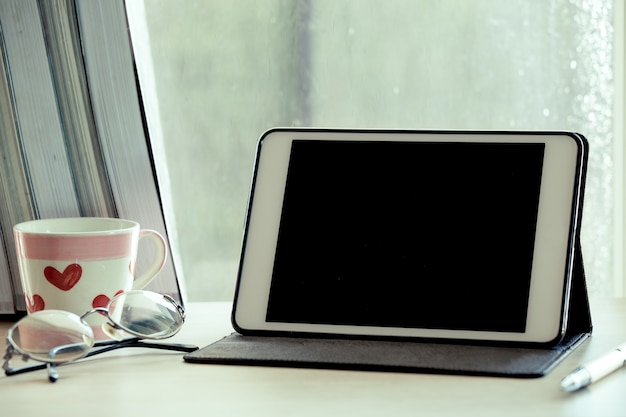 Digital-tablette auf tabelle an dem arbeitsplatz am regnerischen tagesfensterhintergrund im weinlesefarbton
